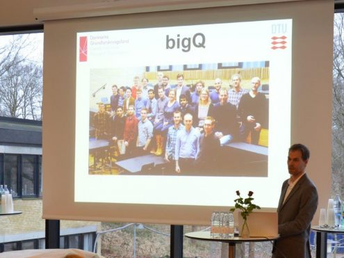 On the picture is head of center Ulrik Lund Andersen in front of a picture of the BigQ team. (Photo: DTU)