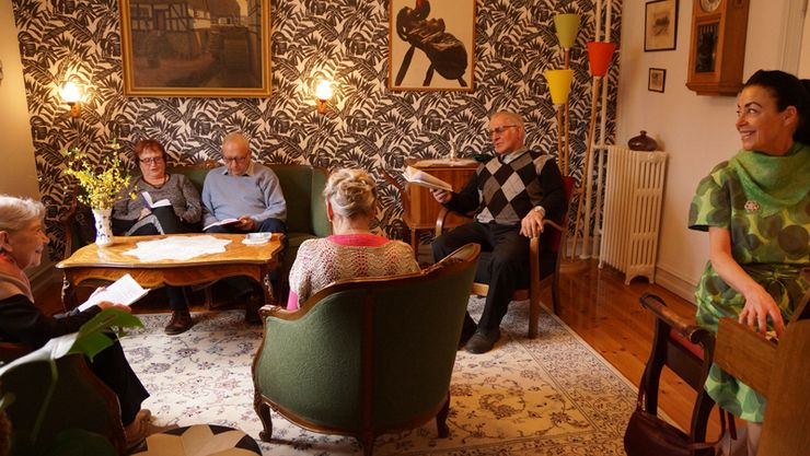 Here a couple of guests are pictured during their visit at Den Gamle By in Aarhus, in the setting of a living room in a typical 1950's home in Denmark.