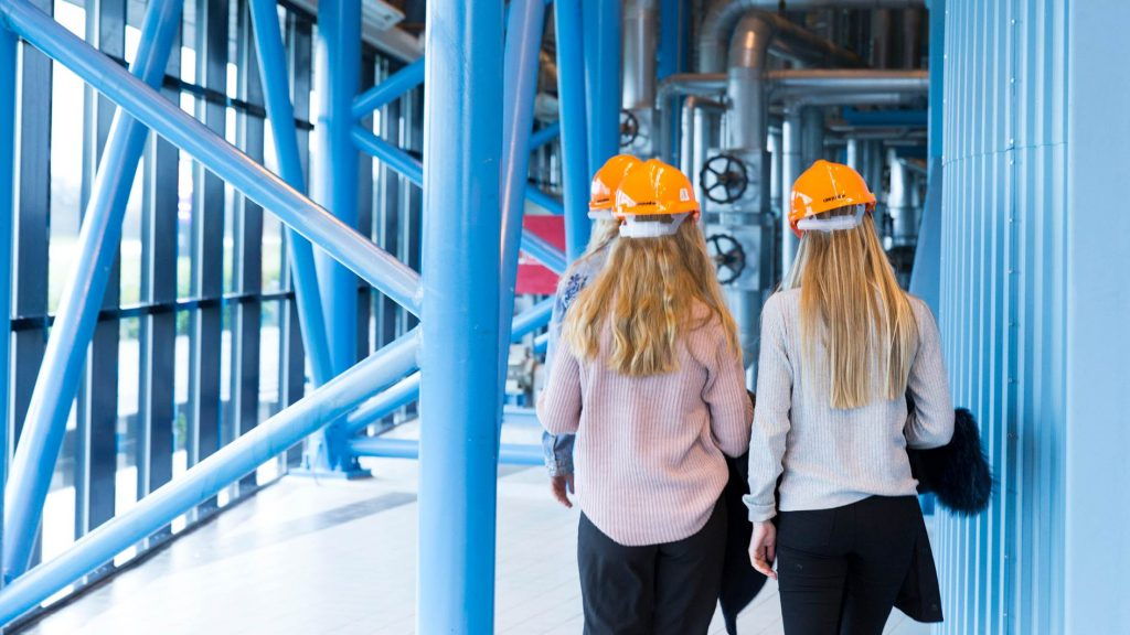 The image shows three pupils wearing orange helmets as they walk in industrial surroundings.